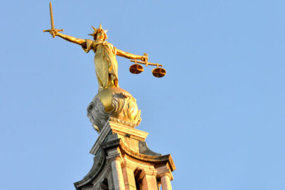 Image of a statue of Justice, holding scales