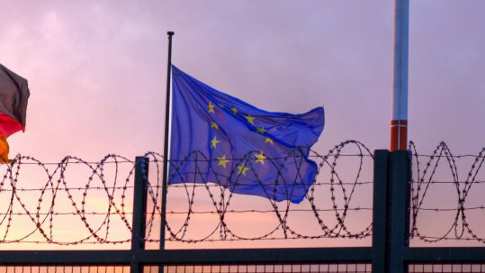 The flag of the European Union flying in from of barbed wire